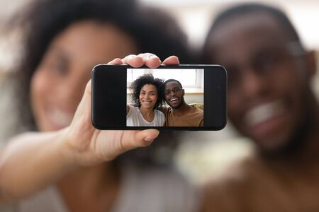 Smiling biracial couple look at camera posing for self-portrait picture using modern smartphone, happy african American husband and wife make selfie on cellphone gadget, new technology users Stockfoto