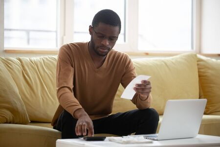 Concentrated african American man sit on couch at home managing paperwork bills calculating household expenses, focused biracial male busy counting taxes or house expenditures, take care of finances 스톡 콘텐츠