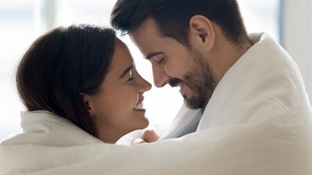 Beautiful happy couple young husband and wife bonding laughing covered with warm blanket, romantic affectionate lovers wrapped in duvet enjoying cozy morning lifestyle at home, close up profile view Foto de archivo - 134601808