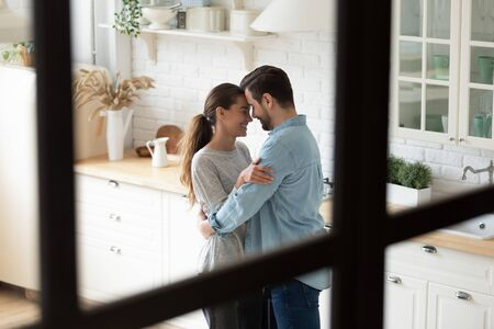 Affectionate young family couple embrace stand in modern kitchen room together, romantic married man and woman bonding dancing enjoy love celebrate anniversary having fun at home, view through window Foto de archivo - 134601813