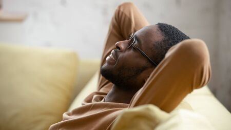 Happy african American young man in glasses sit relax on cozy couch lean hands over head taking nap in living room, smiling biracial male rest on sofa at home sleeping or dreaming, stress free concept Stok Fotoğraf