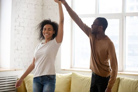 Happy african American young couple relax together dancing waltzing in living room, overjoyed biracial husband and wife have fun swaying at home celebrate moving together, enjoy weekend indoors Stok Fotoğraf