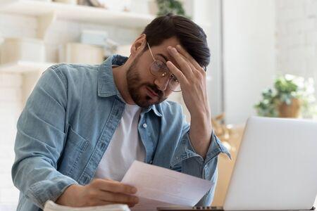 Hombre joven frustrado molesto leyendo malas noticias en el documento de papel de carta de correo postal sentarse en la mesa de casa, chico estresado deprimido preocupado por factura de impuestos de alta factura, problema de dinero de notificación de deuda vencida