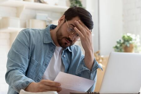 Upset frustrated young man reading bad news in postal mail letter paper document sit at home table, depressed stressed guy worried about high bill tax invoice, overdue debt notification money problem Foto de archivo