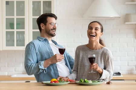 Happy young romantic couple cooking drinking red wine in modern kitchen, cheerful affectionate millennial boyfriend and girlfriend holding glasses enjoying laughing preparing healthy salad at home Foto de archivo - 134601875