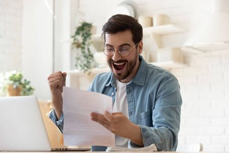Excited euphoric happy young man holding reading paper postal mail letter amazed overjoyed by good news, got new job celebrate taxes refund receive salary payment loan approval sit at home table 版權商用圖片