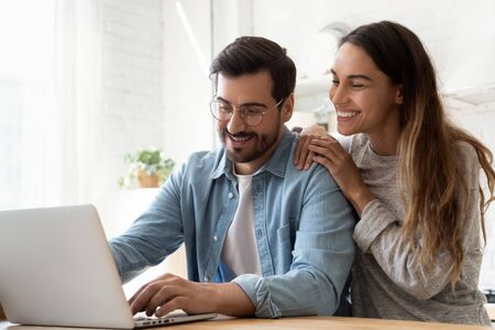 Smiling millennial couple using laptop looking at screen choosing best sale offer sit at home table, happy young husband and wife browse internet social media online enjoy wireless technology device Foto de archivo - 134601887