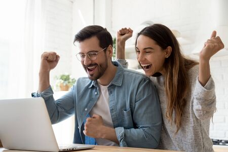 Excited overjoyed young family couple winners feel lucky got sale discount offer by email look at laptop screen celebrate online victory internet auction bid lottery win in app computer technology
