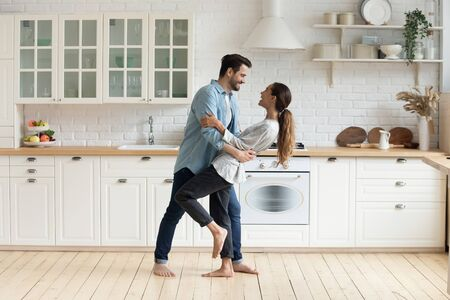 Happy romantic young couple bonding dancing in modern kitchen with white furniture enjoy sweet moments of affection, cheerful husband and wife celebrating anniversary having fun at home lifestyle Foto de archivo - 134572693