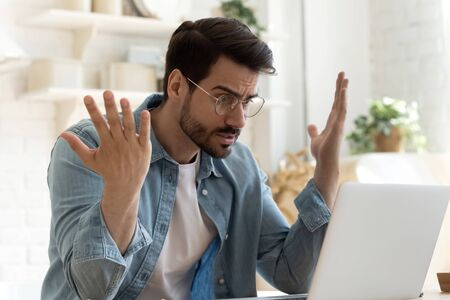 Angry frustrated annoyed young adult man consumer feel rage looking at computer notebook screen furious about laptop pc problem, bad software failure, system virus or malfunction sit at home table 스톡 콘텐츠