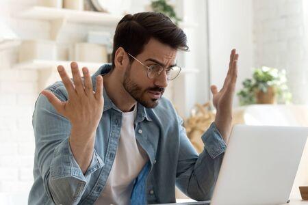 Wütend, frustriert, verärgert, verärgerter junger erwachsener Mann, der Verbraucher wütend auf den Bildschirm eines Computer-Notebooks sieht, der wütend über ein Laptop-PC-Problem, einen schlechten Softwarefehler, einen Systemvirus oder eine Fehlfunktion am heimischen Tisch sitzt