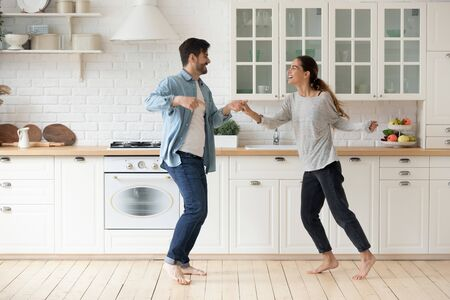 Happy couple having fun dancing together in modern kitchen enjoying lifestyle, active funky young husband and wife first time home buyers moving listening music laughing celebrating freedom party Foto de archivo - 134572711