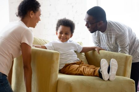 Overjoyed african American young parents hold chair carry furniture with cute little toddler son sitting, happy biracial family settle decorate new home moving with small child, relocation concept