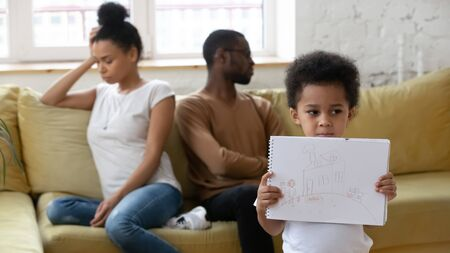 Sad little biracial boy stand holding painted picture of happy family, suffer from parents argue and fight, upset small african American child struggle, psychological effect of breakup or divorce Banco de Imagens
