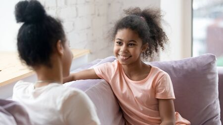 Happy little girl sit on couch with young mom or nanny talking or chatting, gossiping on weekend at home, smiling small child relax on sofa with mother, share secrets with parent, bonding concept