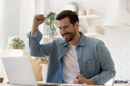 Excited young man winner sit at home table looking at laptop screen celebrating online success victory euphoric overjoyed by internet sport bet win got new job opportunity or loan approval in email