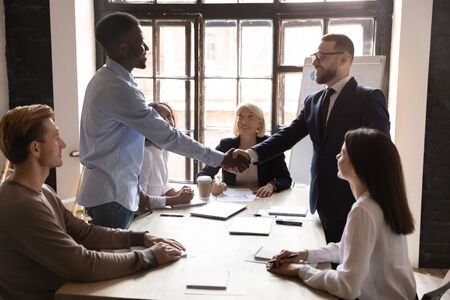 Smiling older and younger mixed race colleagues watching confident team leader shaking hands with smiling african american employee, praising thanking for good job results at meeting in office.