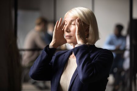 Head shot close up stressed middle aged businesswoman massaging temples, suffering from headache. Unhealthy female older mature leader entrepreneur partner manager feeling exhausted at office.