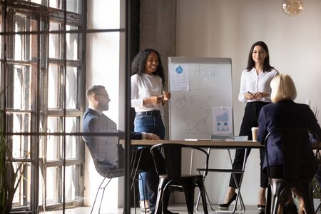 Cheerful african young speaker explaining project details to attentive colleagues at meeting. Pleasant mixed race professionals giving educational lecture seminar to focused teammates in office. Stock Photo