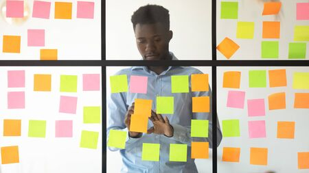 Concentrated african american young manager adding tasks on colorful stickers on glass wall at office. Focused mixed race professional checking working progress, using kanban board at workplace. 写真素材