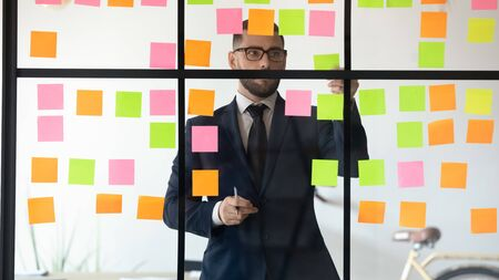 Concentrated young project manager in eyeglasses wearing suit, working near kanban board. Focused confident professional checking processes, using colorful sticky paper on glass wall at office. 写真素材