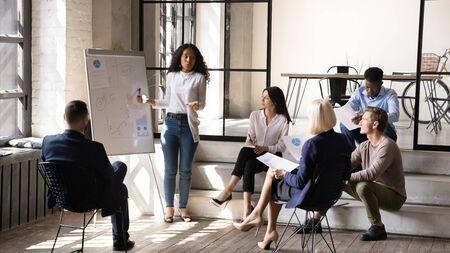 Conférencière sérieuse de jeune femme d'affaires d'origine africaine présentant les résultats de la recherche avec des graphiques sur tableau blanc, expliquant la stratégie marketing de l'entreprise à divers collègues de différentes générations. Banque d'images
