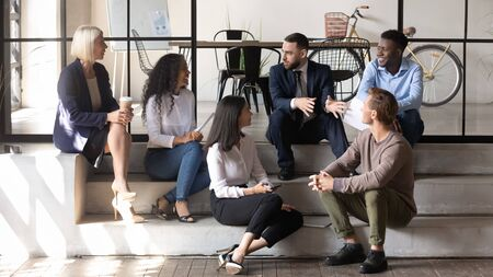 Joyful diverse older and young colleagues sitting on stairs in loft office, listening to confident friendly leader. Relaxed different generations multiracial business people enjoying pause break. Stock Photo - 135118891