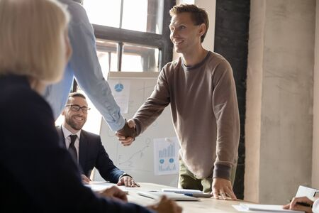 African entrepreneur shaking hands with smiling professional coach, thanking for useful educational workshop at office. Confident mixed race business people welcoming happy client at meeting.