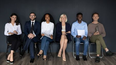 Full length diverse smiling business people sitting in line on chairs, isolated on black wall. Portrait of happy mixed race mature and young company staff, group of managers, sales team, hr concept.