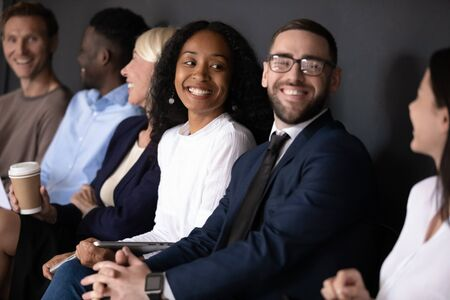 Focus on happy young african american woman sitting in row line with diverse business people, listening to smiling lady. Motivated mixed race job applicants communicating in queue before interview. Stock Photo - 134777296