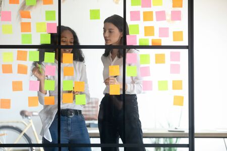 Successful young multiracial female coworkers standing behind glass wall, discussing working processes, adding colorful stickers with notes. Mixed race managers working together near kanban board. 写真素材