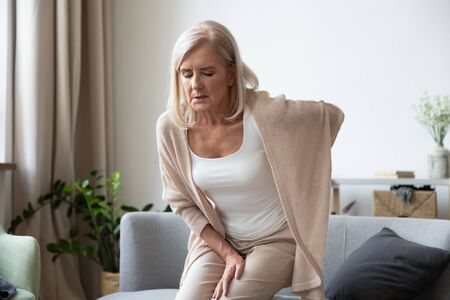 Elderly 60s woman got up from couch felt severe painful feelings in lumbar, massaging low back to reduce ache, suffer from backache discomfort, diseases of older people, sciatic nerve injury concept Reklamní fotografie
