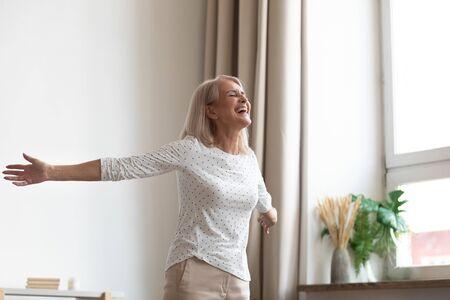 Lachende sorglose Frau mittleren Alters, die im Wohnzimmer steht, streckte die Hände, schloss die Augen, atmete frische Luft, fühlt sich glücklich und gesund an, beginnt einen neuen Tag mit positiver Stimmung und Gedanken, tanzt und genießt das Lebenskonzept Standard-Bild