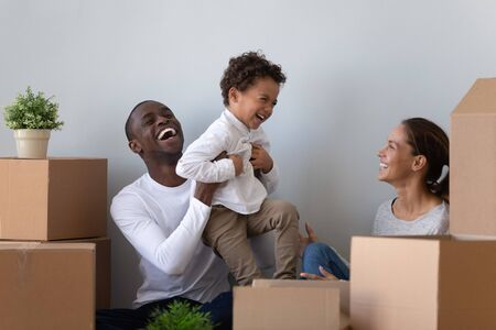 Happy laughing african american young man rising up joyful mixed race cute little son, having fun with wife. Overjoyed smiling multiracial family playing near carton packages, moving in first home.