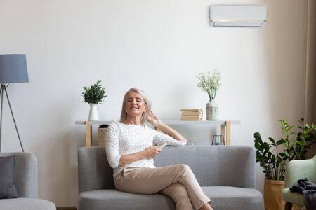 50er Jahre Frau ruht auf der Couch geschlossene Augen genießen frische Luft halten Fernbedienung verwenden Klimaanlage kühlt sich an heißen Sommertagen Temperaturanpassung im Wohnzimmer, Komfort-Wohlfühl-Lebenskonzept Standard-Bild