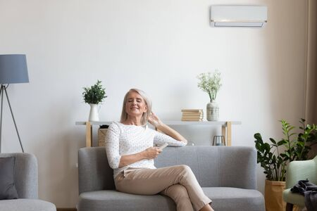 50s woman rest on couch closed eyes enjoy fresh air hold remote control use air conditioner cools herself at summer hot day adjusting temperature inside of living room, comfort wellbeing life concept