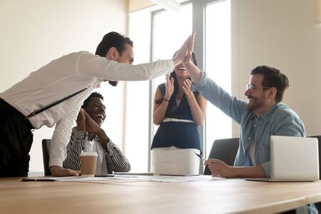 Happy multiracial department celebrating successful project accomplishment, guys team leaders giving high five feels excited, unity, sharing common success, reward and promotion career growth concept Imagens