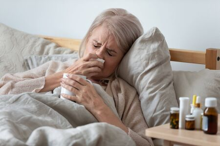 Having cold elderly woman lying in bed under warm blanket holding cup with hot tea beverage sneezes blow runny nose in handkerchief feel unhealthy, heap of medications bottle of pills on bedside table
