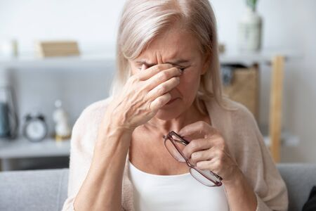 Elderly woman crying wipes tears with hands feels unhappy, bad news. Middle-aged woman taking off glasses closed eyes rubbing eyelid suffers from eye strain deterioration eyesight with age concept Stockfoto