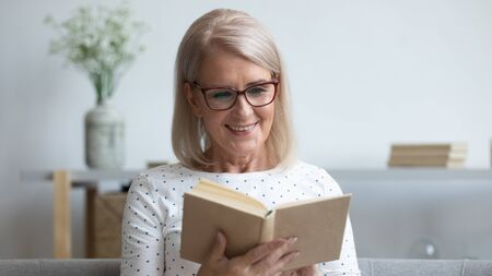 Horizontal image elderly woman in glasses sitting on sofa reading new interesting book. Pastime and favourite hobby of older generation people, ad of bookshop sell buy of bestseller literature concept