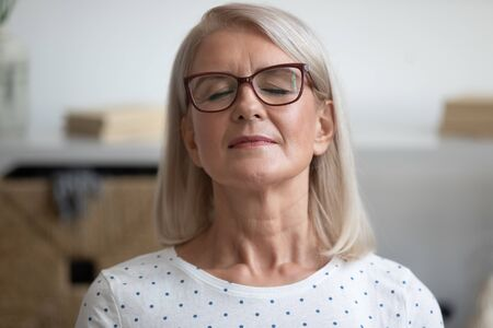 Close up portrait calm 60s middle-aged woman in glasses closed eyes resting seated indoor, concept of free time, freedom and carefree lifestyle, no stress, not hurry enjoy life and moment here and now