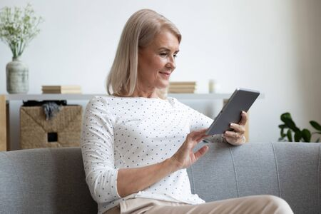 Attractive aged woman sitting on couch using tablet computer reading media news on-line, chatting with friends distantly, having fun in internet, buying in commercial sites, surfing websites concept