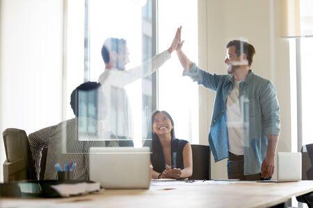 Bekijk door glazen scheidingswand twee jongens die voor diverse collega's staan en handen opsteken die high five geven, elkaar begroeten of respect uitdrukken, bedanken voor het verrichte werk, gemeenschappelijk succesconcept delen Stockfoto