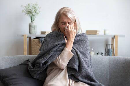 Chora, zamrożona kobieta w średnim wieku 50, siedząca na kanapie w salonie pokryta ciepłą kratą, kichająca, trzymająca papierową serwetkę, zdmuchnąć katar, czuć się niezdrowo, sezonowo zimno, osłabiona koncepcja układu odpornościowego