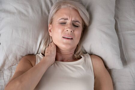 Top close up view middle-aged woman lying in bed in morning feels pain in neck after night sleep, awaken having painful sudden ache or stiffness, incorrect posture during asleep, soft mattress concept
