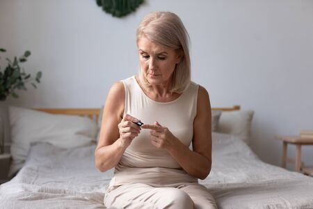 Elderly woman sit on bed in morning holding glucose meter lancets needles pricks skin obtain blood sample, diabetic patient easily do check up control of blood sugar levels at home, diabetes concept