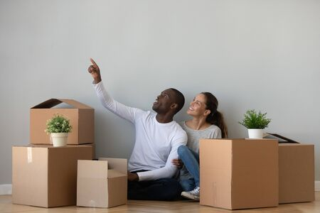 Joyful young african american man sharing renovating or interior ideas with happy wife, sitting on floor between big cardboard boxes. Excited mixed race family planning decoration of new modern home.
