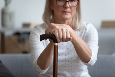Middle-aged woman lost in sad thoughts seated on couch holding in hands cane close up focus on walking stick tool, concept of old human diseases causing movement disorder, rehabilitation, healthcare