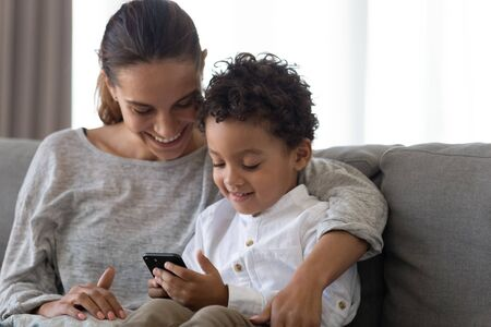 Happy young mother embracing small preschool mixed race cute kid son, sitting on couch at home together, using educational applications on smartphone, playing online games or watching funny cartoons.