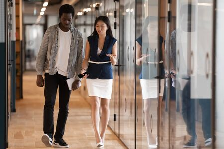 Asian female boss african worker walk in office hallway discuss new business opportunities project details, multi-ethnic colleagues having friendly relations chatting during break met in hall concept